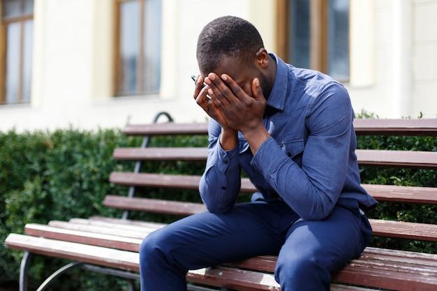 Cansado hombre afroamericano se sienta en el banco fuera