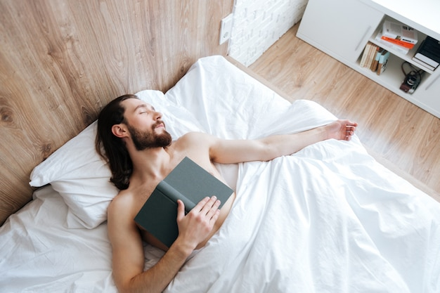 Cansado joven barbudo con libro durmiendo en la cama