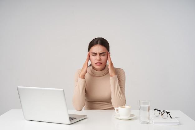 Cansado joven bastante mujer de pelo oscuro sosteniendo los dedos índices en sus sienes mientras sufre de dolor de cabeza, manteniendo los ojos cerrados mientras posa sobre una pared blanca