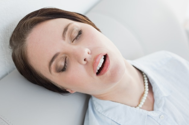 Cansado mujer bien vestida sentado y durmiendo en el sofá