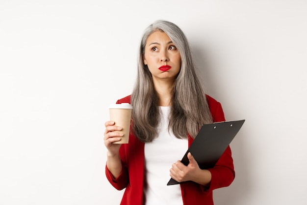 Cansado oficinista asiática sosteniendo portapapeles y vaso de papel, tomando café y exhalando con la cara exhausta, de pie sobre fondo blanco.
