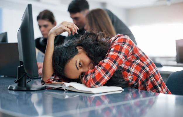 Cansado un poco. grupo de jóvenes en ropa casual que trabajan en la oficina moderna