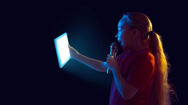 Cantando para vlog. retrato de niña caucásica sobre fondo oscuro en luz de neón. modelo femenino hermoso que usa la tableta. concepto de emociones humanas, expresión facial, ventas, publicidad, tecnología moderna, gadgets. volantes.