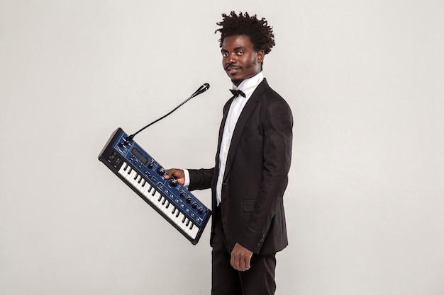 Cantante africana de moda con peinado afro en esmoquin de estilo clásico negro y pajarita con sintetizador, mirando a la cámara. interior, tiro del estudio aislado sobre fondo gris