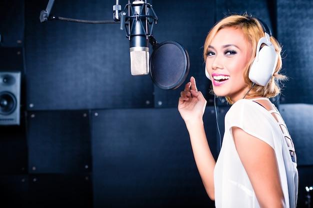 Cantante asiática produciendo canción en estudio de grabación.