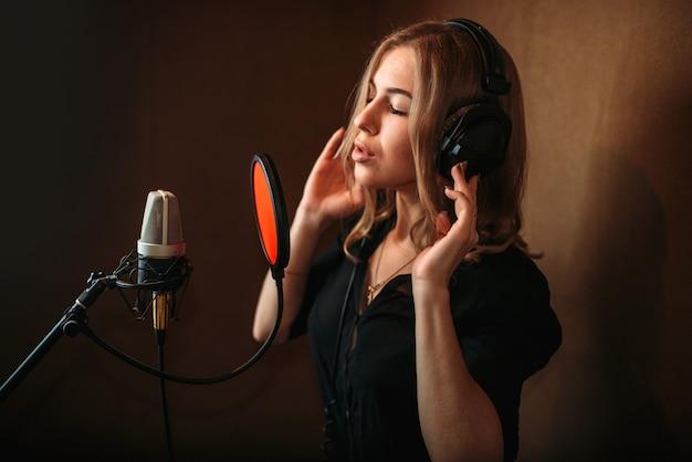 Cantante grabando una canción en el estudio de música