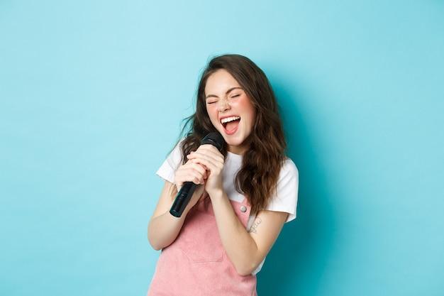 Cantante hermosa chica sosteniendo el micrófono, cantando karaoke en micrófono, de pie sobre fondo azul.