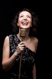 Cantante hermosa feliz de la muchacha que ríe el micrófono retro de la explotación agrícola
