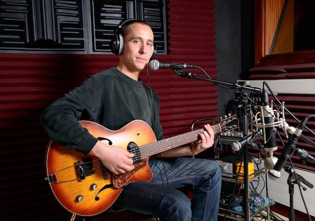 Un cantante y su guitarra en un estudio de grabación.
