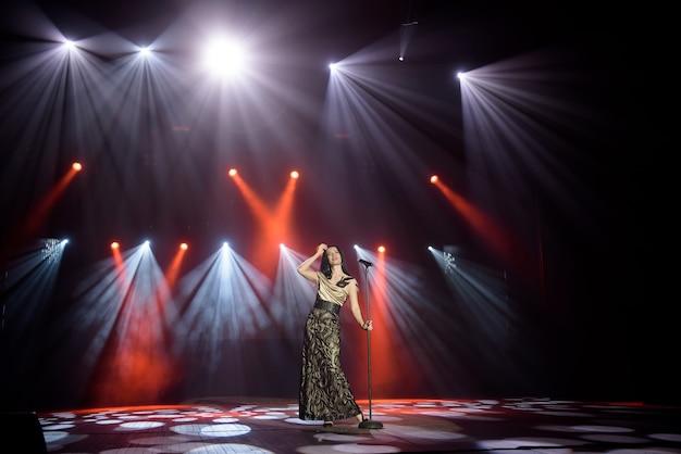 Cantante con un vestido en el escenario bajo los rayos de luz brillante con humo.