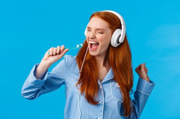 Cante como si nadie lo viera. mujer pelirroja alegre y despreocupada alegre en pijama, con auriculares grandes