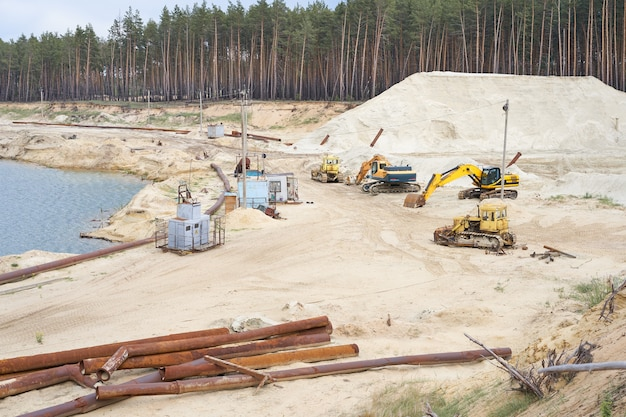 Cantera de arena, equipo de la industria minera, excavadora, tractor, tierra de arena permanente cerca del agua del lago