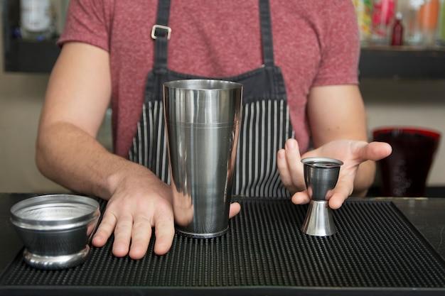 El cantinero agrega ingrediente en la coctelera en el mostrador de la barra
