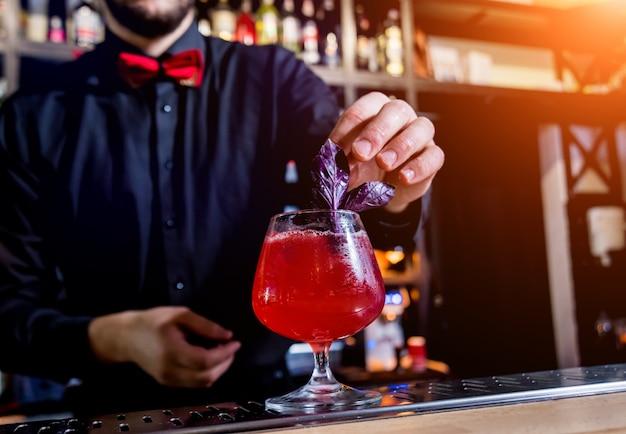 El cantinero está haciendo un cóctel en la barra del bar. cócteles frescos