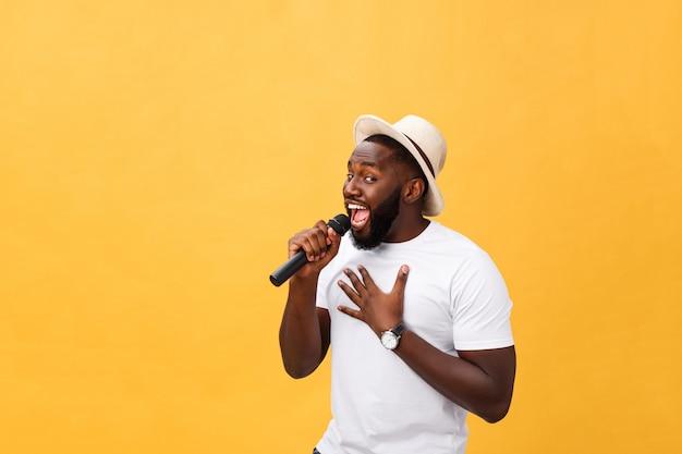 Canto afroamericano hermoso joven del muchacho emocional con el micrófono aislado en fondo amarillo