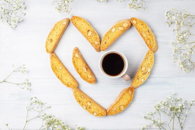 Cantuccini, galletas tradicionales toscanas italianas con almendras, una taza de café a la luz