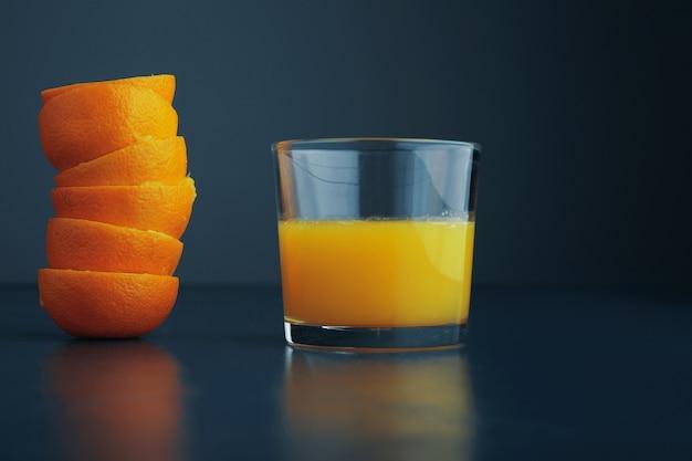 Capa de cáscara de mandarina cerca del vidrio con jugo de naranja cítrico fresco y saludable para el desayuno, aislado en la vista lateral de la mesa azul rústica