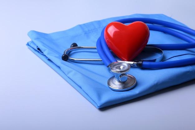 Capa del doctor con el estetoscopio médico y el corazón rojo en el escritorio