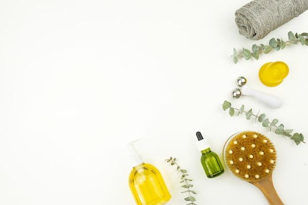 Una capa plana de aceite facial y rodillo facial, cepillo para masaje, toalla de algodón y brunches de eucalipto.