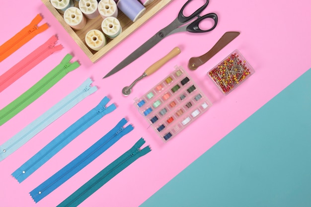 La capa plana de material de costura contiene las tijeras, cinta métrica, cremallera y rollos de hilo.
