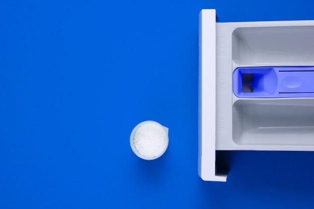 Capacidad de lavadora para polvo, recipiente medidor con polvo sobre fondo azul. vista superior, endecha plana