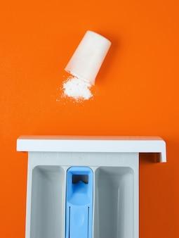 Capacidad de lavadora para polvo, recipiente medidor volcado con polvo sobre fondo naranja. vista superior, endecha plana