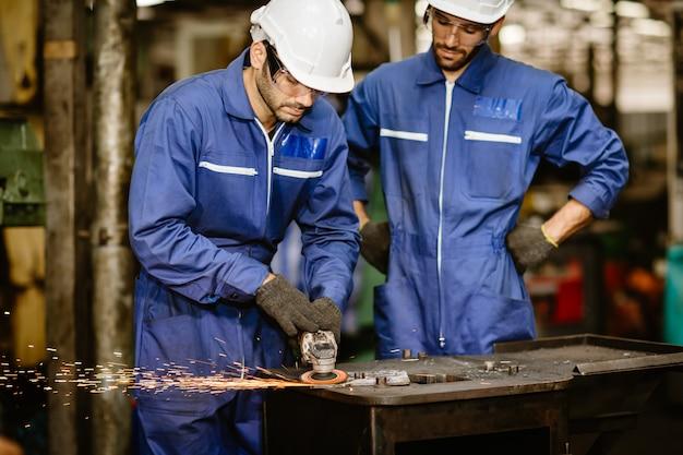 Capacitación de trabajadores senior y observe a un joven aprendiz joven usar herramientas para la seguridad en trabajos industriales de corte de acero.