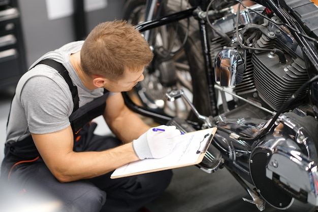 Capataz en el centro de reparación de servicio diagnostica piezas en motocicleta