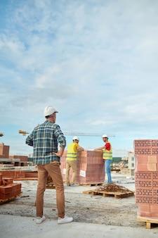 Capataz inspeccionando el trabajo de dos jóvenes constructores