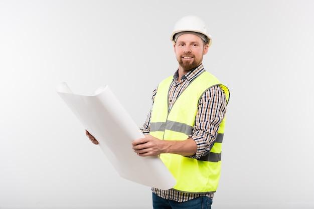 Capataz joven exitoso en casco protector y ropa de trabajo sosteniendo el plano frente a sí mismo mientras lo mira