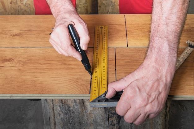 Un capataz con un mono rojo marca el laminado con una regla y un rotulador antes de cortar.