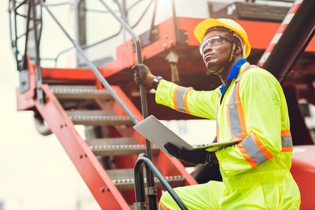 El capataz del personal africano negro tiene la intención de trabajar con el trabajador de carga utilizando una computadora portátil para controlar el envío de carga en el almacén logístico.