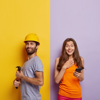 El capataz satisfecho usa casco protector amarillo, sostiene un martillo, repara algo en casa