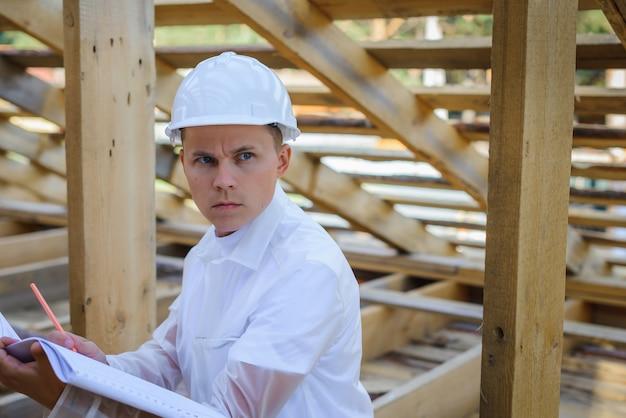 Capataz vestido de blanco inspecciona el área de construcción. arquitecto con plano de marco de madera.