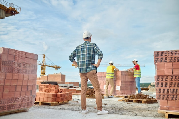Capataz viendo a los trabajadores apoyado en la pila de ladrillos rojos