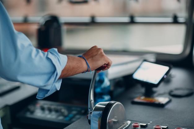 El capitán del barco sostiene su mano sobre el interruptor de velocidad
