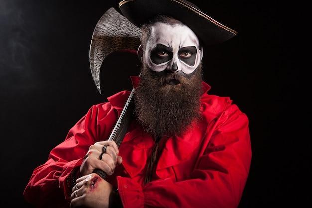 Capitán medieval sosteniendo un hacha sobre fondo negro. traje de halloween.