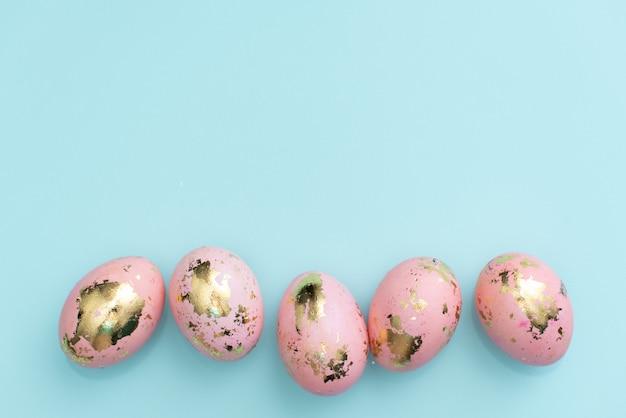 Capítulo de los huevos adornados de oro de pascua en fondo azul en colores pastel.