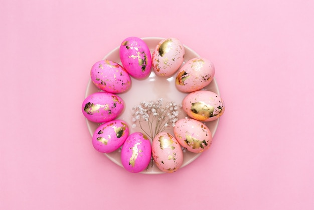 Capítulo de los huevos adornados de oro de pascua en fondo del rosa en colores pastel.