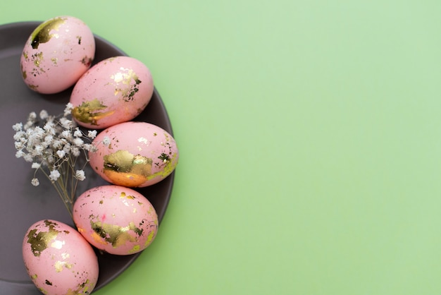 Capítulo de los huevos adornados de oro de pascua en fondo verde en colores pastel.