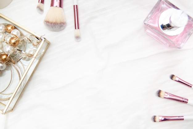 Capítulo para el texto hecho de rosa maquillaje profesional pinceles de perfume perlas y pendientes en la caja sobre fondo blanco.