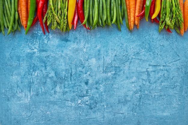 Capítulo de verduras coloridas en fondo azul brillante.
