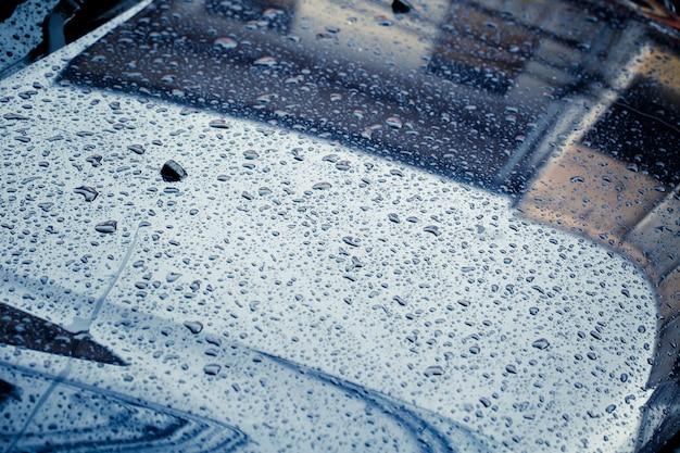 Capota del coche con gota de lluvia húmeda limpia oscuro tono de color de tormenta en la temporada de lluvias