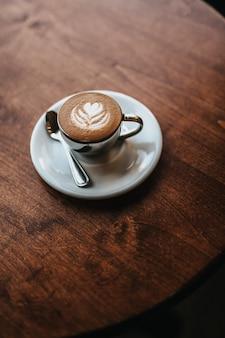 Cappuccino bellamente hecho servido con arte floral en el tiro de espuma desde la vista aérea