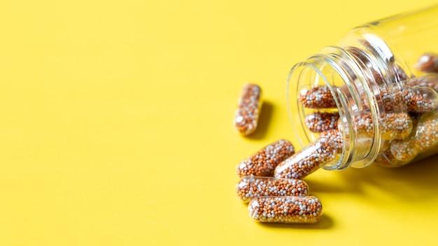 Cápsula de multivitaminas y suplementos con frutas frescas y saludables sobre fondo amarillo,