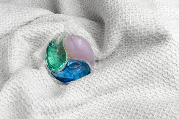 Cápsula de tres colores para lavar la ropa sobre un paño blanco
