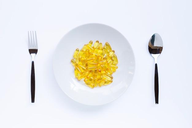 Cápsulas de aceite de pescado en plato blanco, folk y cuchara