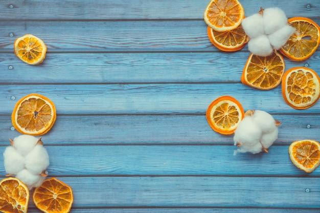 Cápsulas de algodón y naranjas dired en mesa de madera azul