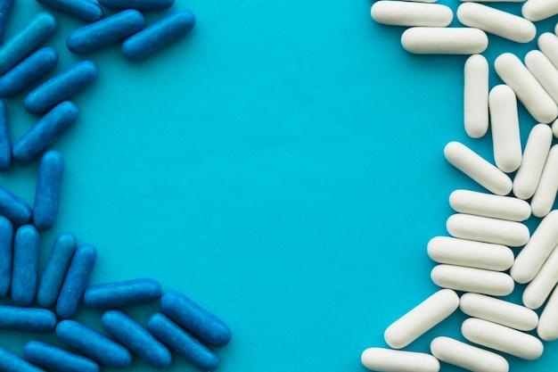 Cápsulas de caramelo blanco y azul formando marco sobre fondo cian
