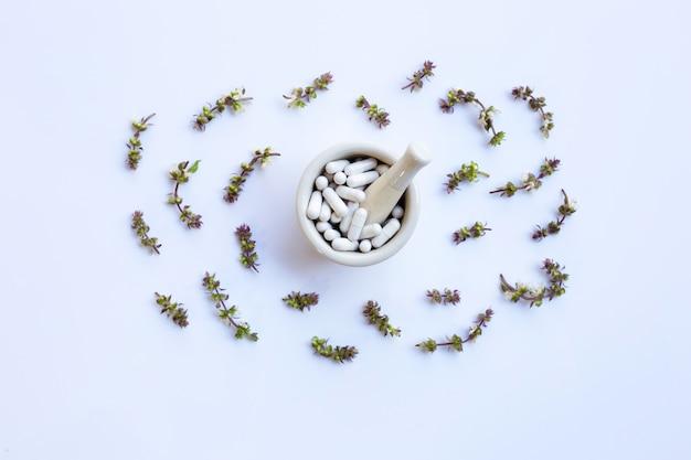 Cápsulas de hierbas medicinales con flor de albahaca dulce